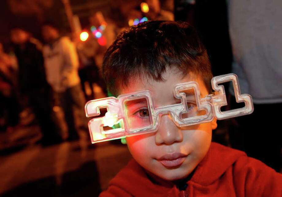 Michael Guardado, 4, joins New Year's Eve revelers at the Celebrate S.A. New Year's Eve party downtown on Friday, Dec. 31, 2010. Guardado was with family to see the fireworks finale at midnight. Photo: KIN MAN HUI, SAN ANTONIO EXPRESS-NEWS / kmhui@express-news.net