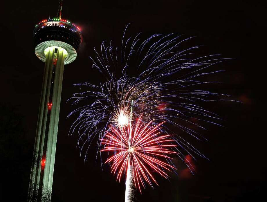 Fireworks erupt near the Tower of Americas to celebrate the New Year 2011 in San Antonio. Photo: KIN MAN HUI, SAN ANTONIO EXPRESS-NEWS / kmhui@express-news.net