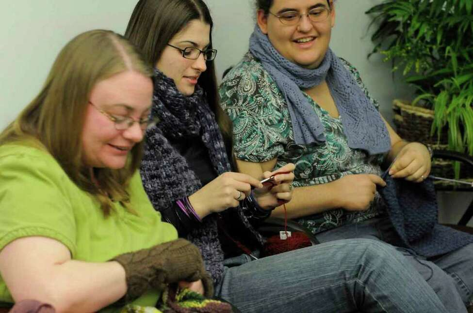 Left to right, Annie Heavener, Monika Mundel and Susan Beckhardt take part in a knitting group with UAlbany international students in which they improve their English language skills as they knit socks, scarves, hats in Albany 12/14/2010. Heavener is advisor for the International Student and Scholar Services and runs the knitting group.( Michael P. Farrell/Times Union )