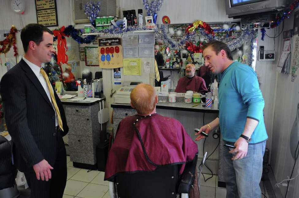 Town of Clarkstown Town Clerk David Carlucci will be the youngest state Senator, at age 29, in the 2011 session. He appears at his longtime barbershop, Sal's Barber Shop, near his office in the hamlet of New City in Rockland County. Carlucci talks with 35-year customer Jan Hochbaum, center, and the shop's current owner Aron Aronov, right, who bought the shop from the original owner. ( Philip Kamrass / Times Union )