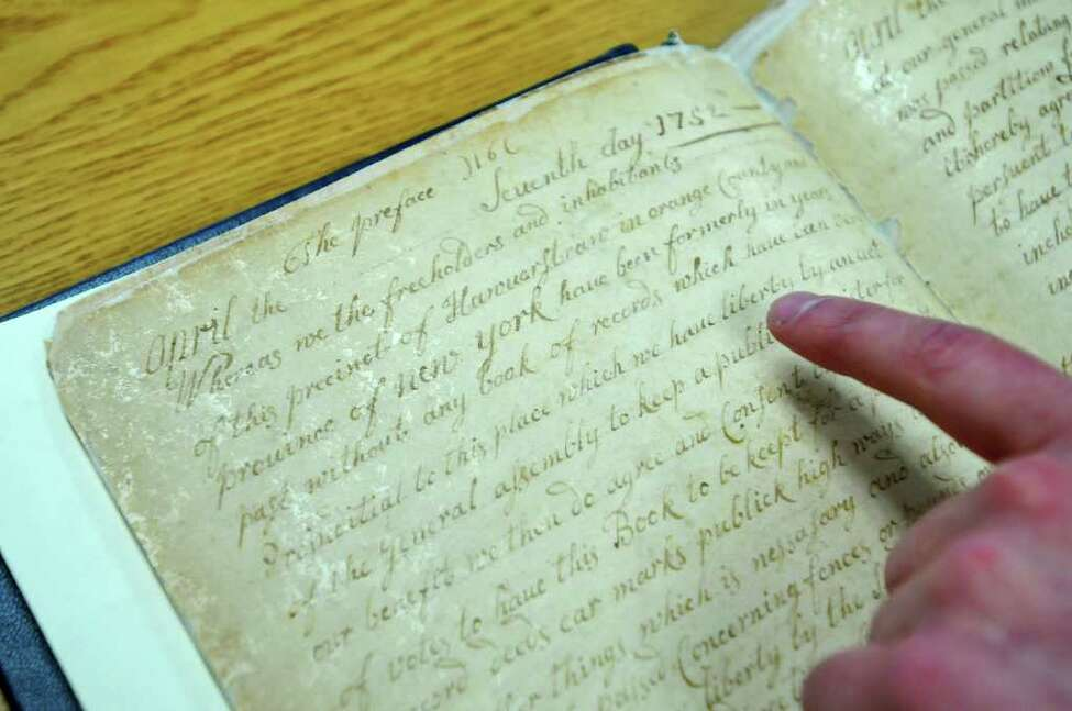 Town of Clarkstown Town Clerk David Carlucci looks at a hand-written record from 1752. The record was written before the town was created. He has overseen the digital conversion of town records. He moves to the state Senate as its youngest member in the 2011 session. ( Philip Kamrass / Times Union )