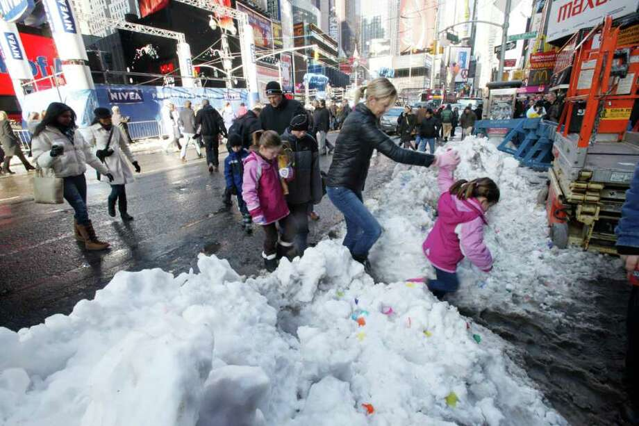 n this Dec. 29, 2010 file photo, visitors in New York's Times Square navigate through slush three days after snow fell across every corner of the city. The city has cleaned up from big storms before with ease, but this blizzard became unlike anything New Yorkers had seen in decades.  (AP Photo/Mary Altaffer, File) Photo: Mary Altaffer