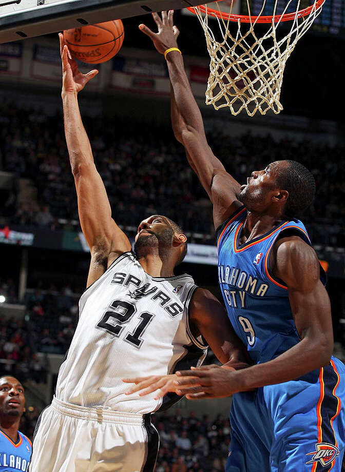 Spurs' Tim Duncan shoots around  Thunder's Serge Ibaka during first half action Saturday. Photo: EDWARD A. ORNELAS/eaornelas@express-news.net