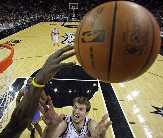 Spurs' Tiago Splitter grabs for a rebound against a Thunder defender during second half action Saturday. Photo: EDWARD A. ORNELAS/eaornelas@express-news.net
