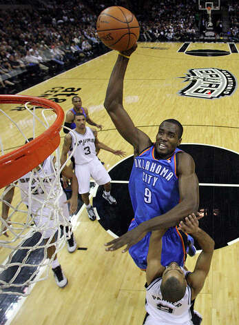 Thunder's Serge Ibaka goes up for a dunk over Spurs' Tony Parker  during second half action Saturday. Photo: EDWARD A. ORNELAS/eaornelas@express-news.net