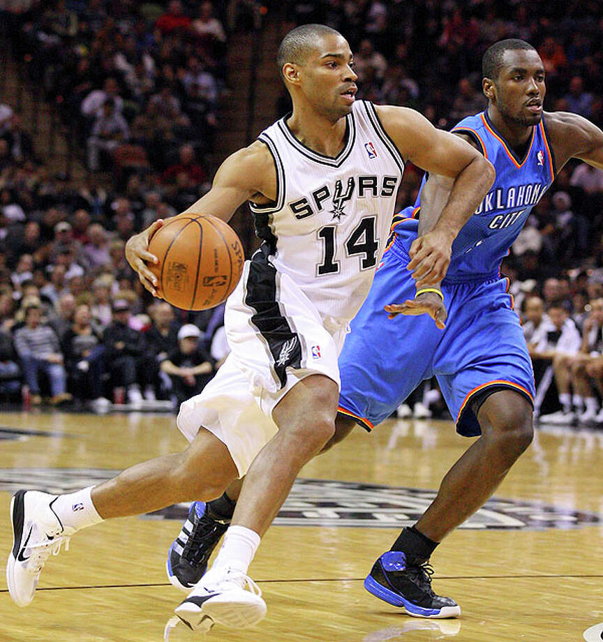 Spurs' Gary Neal looks for room around Thunder's Serge Ibaka during second half action Saturday. Photo: EDWARD A. ORNELAS/eaornelas@express-news.net