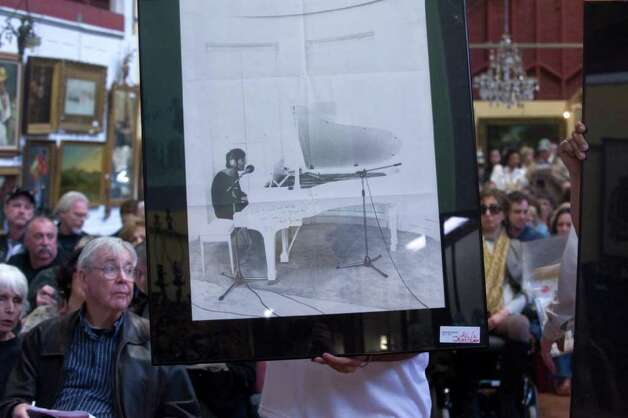 A signed poster of John Lennon goes up for auction during the Braswell Galleries' 24th Annual New Year's Day Auction in Norwalk, Conn., Saturday, January 1, 2011. More than 700 items were on the block including John Lennon's white Abbey Road suit, Imagine jacket and 1972 Chrysler station wagon, which sold for $46,000, $18,000 and $55,000 respectively. Artwork by Pablo Picasso and Damien Hirst also sold. Photo: Keelin Daly / Stamford Advocate