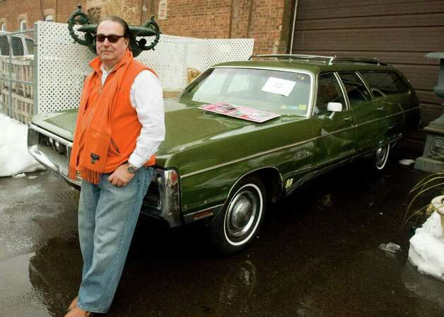 Hank Gioiella poses with his newly acquired 1972 Chrysler station wagon formerly owned by John Lennon at the Braswell Galleries' 24th Annual New Year's Day Auction in Norwalk, Conn., Saturday, January 1, 2011. More than 700 items were on the block including John Lennon's white Abbey Road suit, Imagine jacket and the wagon, which sold for $46,000, $18,000 and $55,000 respectively. Artwork by Pablo Picasso and Damien Hirst also sold. Photo: Keelin Daly / Stamford Advocate