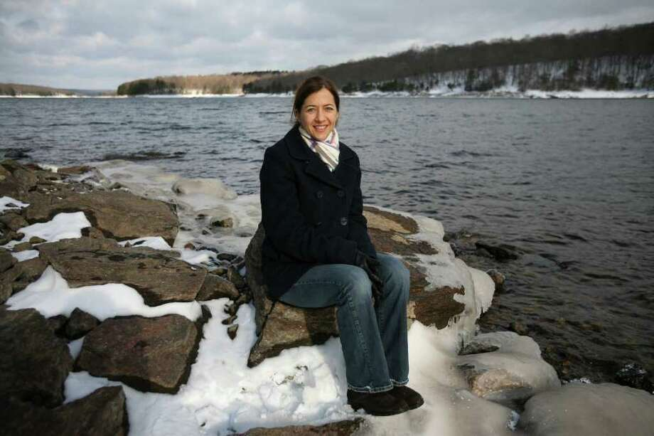 "Author Cathryn Prince of Weston sits on the shore of the Easton Reservoir, where meteorites were found in 1807. The discovery is the subject of her new book ""A Professor, a President, and a Meteor: the Birth of American Science"". Photo: Brian A. Pounds / Connecticut Post"