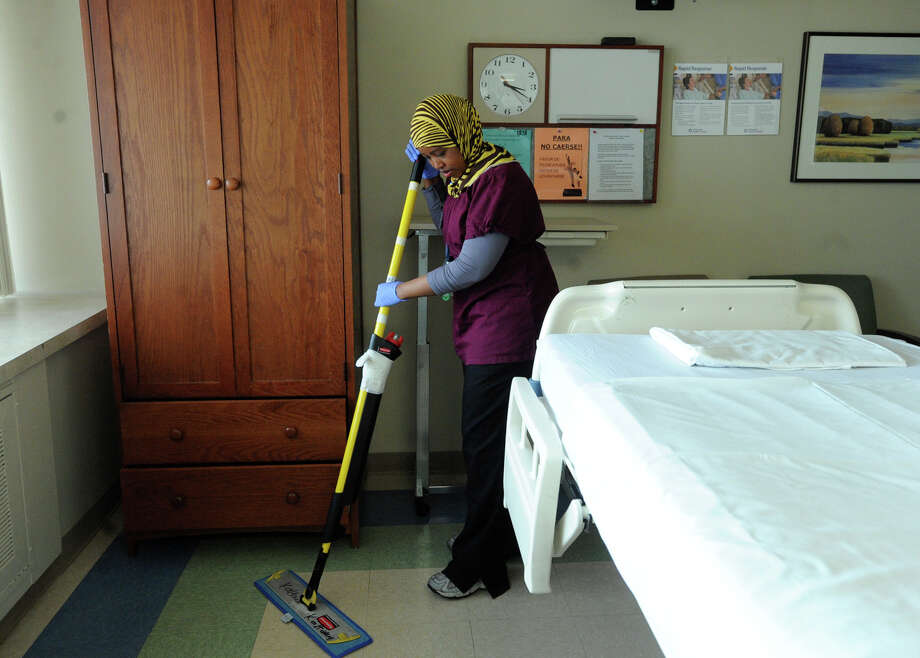 Nuura Maxamded mops a floor at University Hospital. Methodist Healthcare and the University Health System have been working with Catholic Charities to provide employment for refugees. Photo: BILLY CALZADA/gcalzada@express-news.net