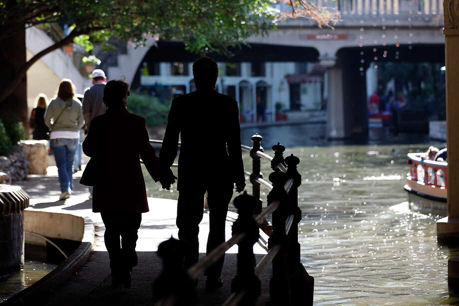 Visitors enjoy the River Walk on Sunday, hours before draining was due to start to ready the tourist attraction for its annual cleanup. Photo: Jerry Lara/glara@express-news.net