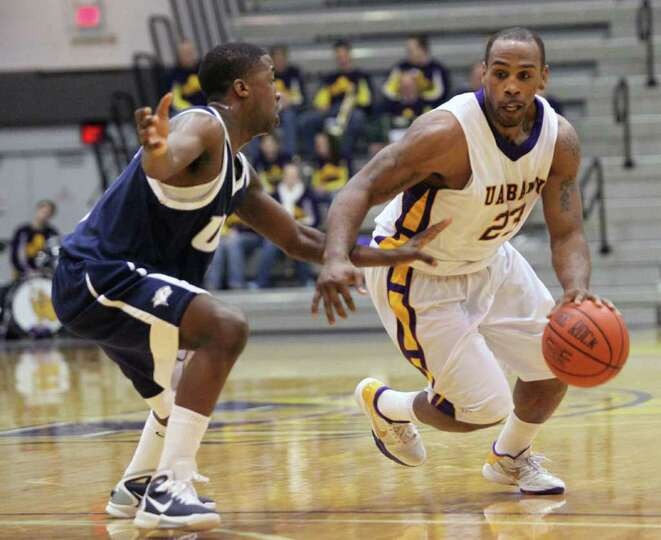UAlbany's Tim Ambrose (23) drives upcourt against New Hampshire's Jordon Bronner (5) during Sunday a