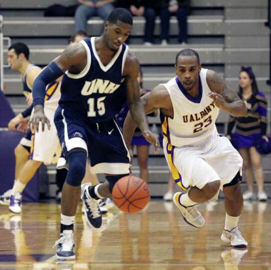 The University at Albany's Tim Ambrose (23) and New Hampshire's Ferg Myrick (15) fight for the ball