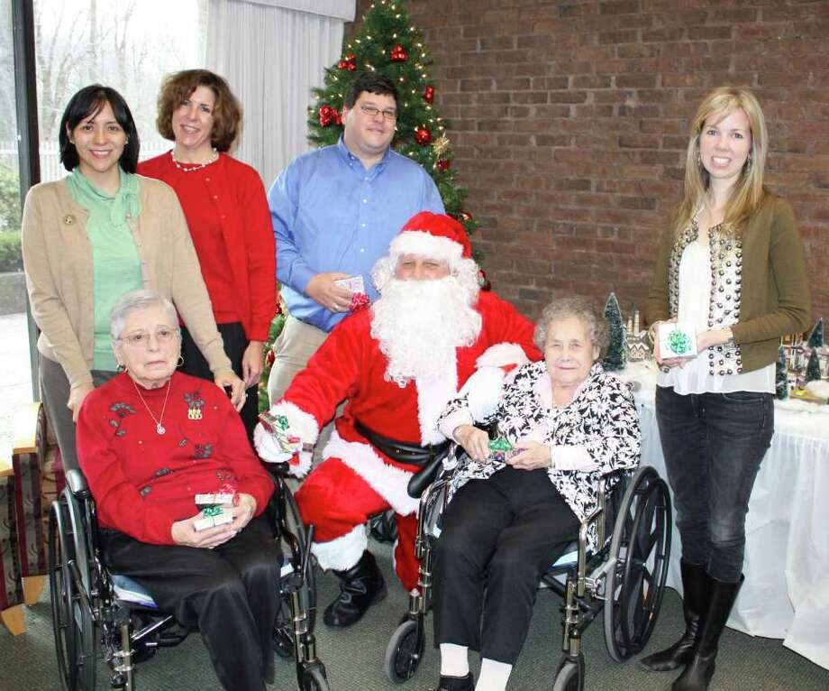 Pennyweights owners Geoff and Kelly Sigg (with Santa) present Care Center residents Elma Fay and Mary Ambrosio with one of the many donated gifts. Also pictured are Heather Neff, Waveny chief executive officer, and Dalila Berlingo, director of therapeutic recreation. Photo: Contributed Photo / New Canaan News