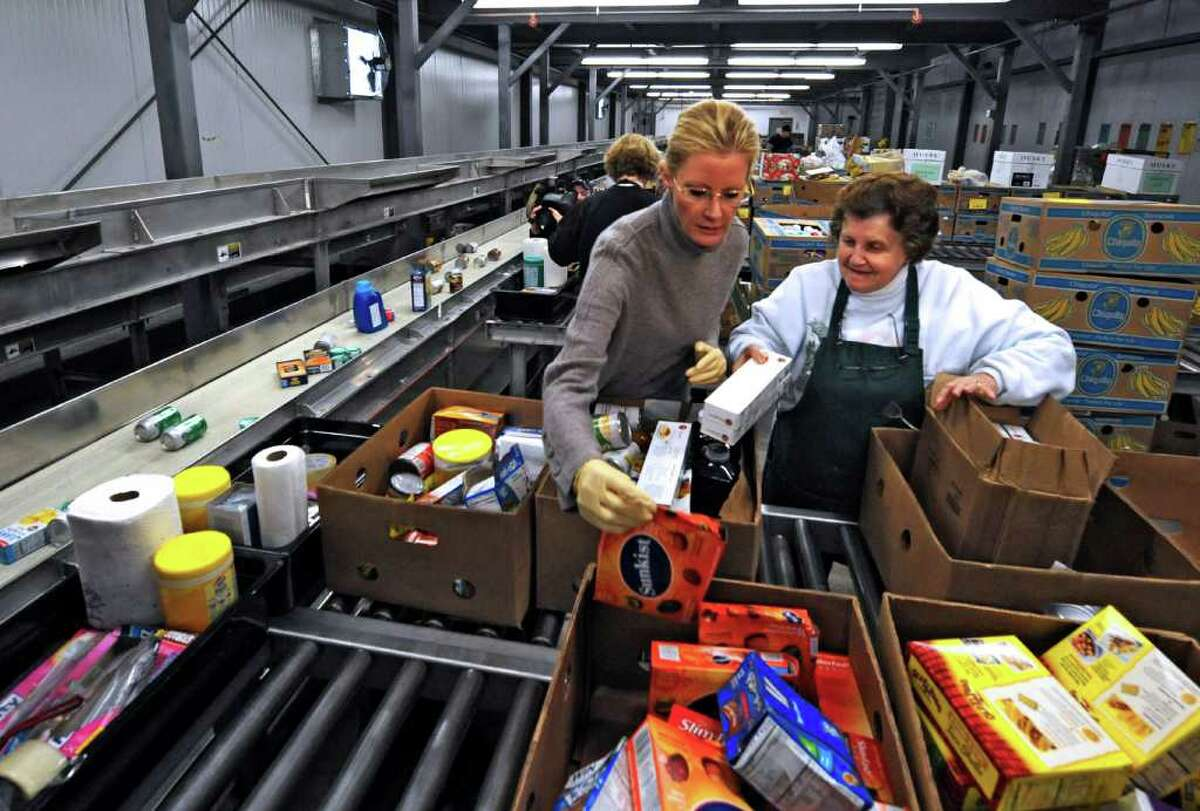 Food Network star Sandra Lee, left, sorts food with Fran Marchesini as she makes a visit to the Regional Food Bank of Northeastern New York in Colonie on January 3, 2011. (Skip Dickstein / Times Union)