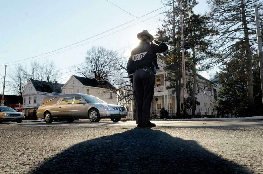 New York State Trooper, Erika Hock, Troop G, SP Brunswick,  salutes as the hearse carrying the body of retired Troy police Sgt. James O'Brien drives away from  Sacred Heart Church in Troy following his funeral on Monday, Jan. 3, 2011.  O?Brien was 47 when he died, and was a key member of the department?s emergency response team.  O'Brien passed away after a long battle with leukemia.  O?Brien joined the police force in 1990 and the emergency response team in 1992.  He was promoted to sergeant in 1994. In 1997, he received the Troy PBA Silver Shield Award.  (Paul Buckowski / Times Union) Photo: Paul Buckowski / 00011605A