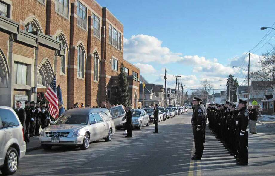 Law enforcement from Troy and the surrounding areas, salute as the casket of retired Troy police Sgt. James O'Brien is carried out of  Sacred Heart Church in Troy following his funeral on Monday, Jan. 3, 2011.   O?Brien was 47 when he died, and was a key member of the department?s emergency response team.  O'Brien passed away after a long battle with leukemia.  O?Brien joined the police force in 1990 and the emergency response team in 1992.  He was promoted to sergeant in 1994. In 1997, he received the Troy PBA Silver Shield Award.  (Paul Buckowski / Times Union) Photo: Paul Buckowski / 00011605A
