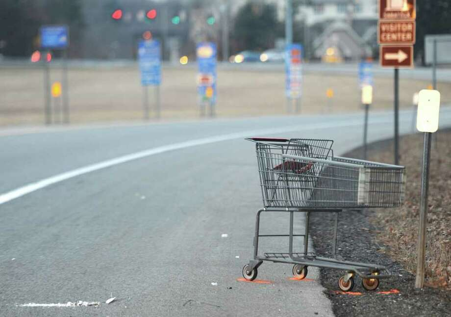 The wheels of a shopping cart are marked as part of the investigation into Monday night's fatal accident near Exit 15 of the Northway. A man was struck by a car and then run over by two tractor-trailers,  State Police said.  (Skip Dickstein / Times Union) Photo: Skip Dickstein / 2008
