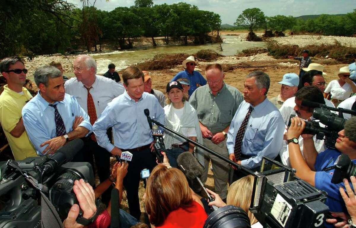 FOR METRO DAILY - U.S. Representative Charles Gonzalez(from left in blue shirt and tie), U.S. Senator Phil Gramm, U.S. Representative Lamar Smith, U.S. Senator Kay Bailey Hutchison, FEMA Director Joe Allbaugh, and U.S. Representative Henry Bonilla answer questions from the media Friday July 12, 2002 in the Horseshoe Falls estates neighborhood near Canyon Lake in Sattler,Tx. The neighborhood was hardhit by the 2002 flood. PHOTO BY EDWARD A. ORNELAS/STAFF