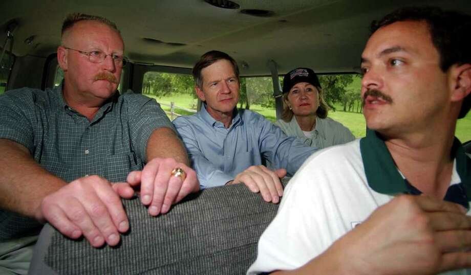 FOR METRO DAILY - FEMA Director Joe Allbaugh(from left), U.S. Representative Lamar Smith, and U.S. Senator Kay Bailey Hutchison talk with New Braunfels Mayor Adam Cork about the 2002 flood during a tour of the flood damaged areas near Canyon Lake Friday July 12, 2002. PHOTO BY EDWARD A. ORNELAS/STAFF Photo: EDWARD A. ORNELAS, SAN ANTONIO EXPRESS-NEWS / SAN ANTONIO EXPRESS-NEWS