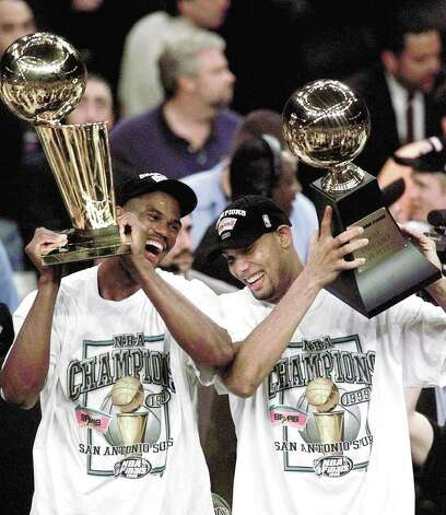 San Antonio Spurs' David Robinson, left, holds the NBA championship trophy as teammate Tim Duncan holds the Most Valuable Player trophy after defeating the New York Knicks 78-77 in Game 5 of the 1999 NBA Finals Friday, June 25, 1999, at New York's Madison Square Garden. Photo: MARK LENNIHAN, AP / AP