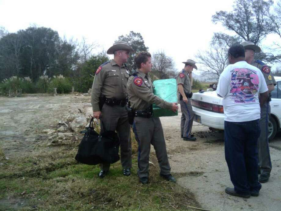 Texas DPS Trooper Brigitte Hazelton, center, confiscates the marijuana found in a Camry that led a chase through Chambers County. Joanne Liou/The Enterprise