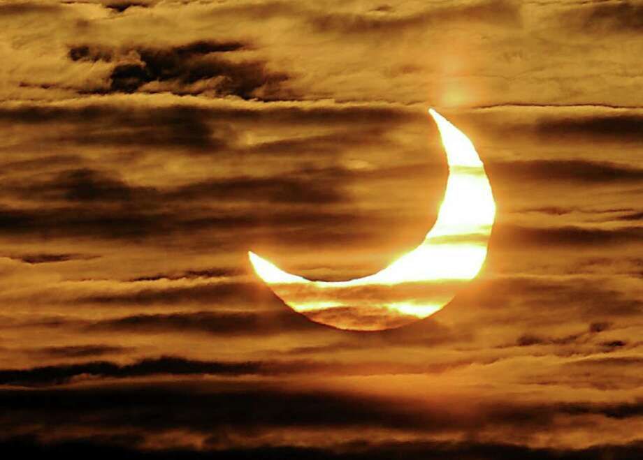 A picture taken on January 4, 2011 in Locon, northern France, shows the world's first partial solar eclipse of 2011. A solar eclipse happens when the Moon swings between the Earth and the Sun. TOPSHOTS    AFP PHOTO PHILIPPE HUGUEN (Photo credit should read PHILIPPE HUGUEN/AFP/Getty Images) Photo: PHILIPPE HUGUEN