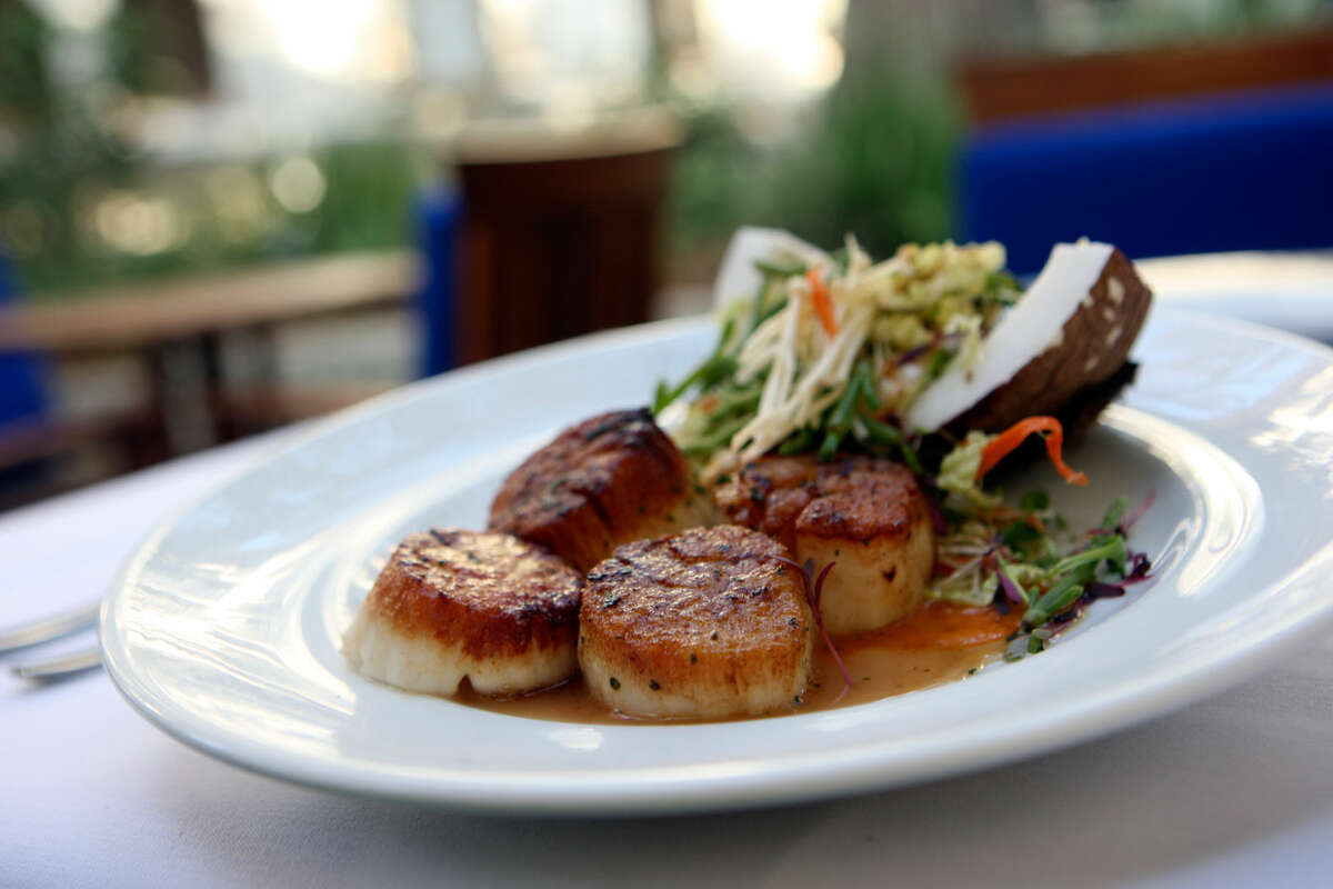 Ostra's scallops, served with spicy cabbage slaw in a wedge of coconut shell, earned raves, although the reason for the coconut shell was never really understood.HELEN L. MONTOYA/hmontoya@express-news.net