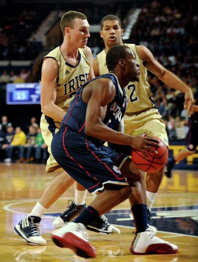 Connecticut guard Niels Giffey drives the lane as Notre Dame guards Ben Hansbrough, left, and Joey Brooks defend during the first half of an NCAA college basketball game Tuesday, Jan. 4, 2011, in South Bend, Ind. (AP Photo/Joe Raymond) Photo: AP