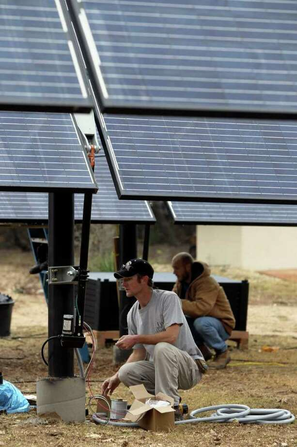 Jay Cockrell, an employee of Novastar Energy, works Thursday on a solar-panel installation at a home north of San Antonio. Photo: JOHN DAVENPORT, SAN ANTONIO EXPRESS-NEWS / jdavenport@express-news.net