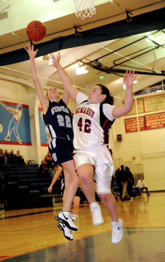 Staples' Nikki Bukovsky, left, puts up a shot as McMahon's Rachel Sawyer, right, blocks during Tuesday's girl's basketball game at Brien McMahon High School in Norwalk on January 4, 2011. Photo: Lindsay Niegelberg / Connecticut Post