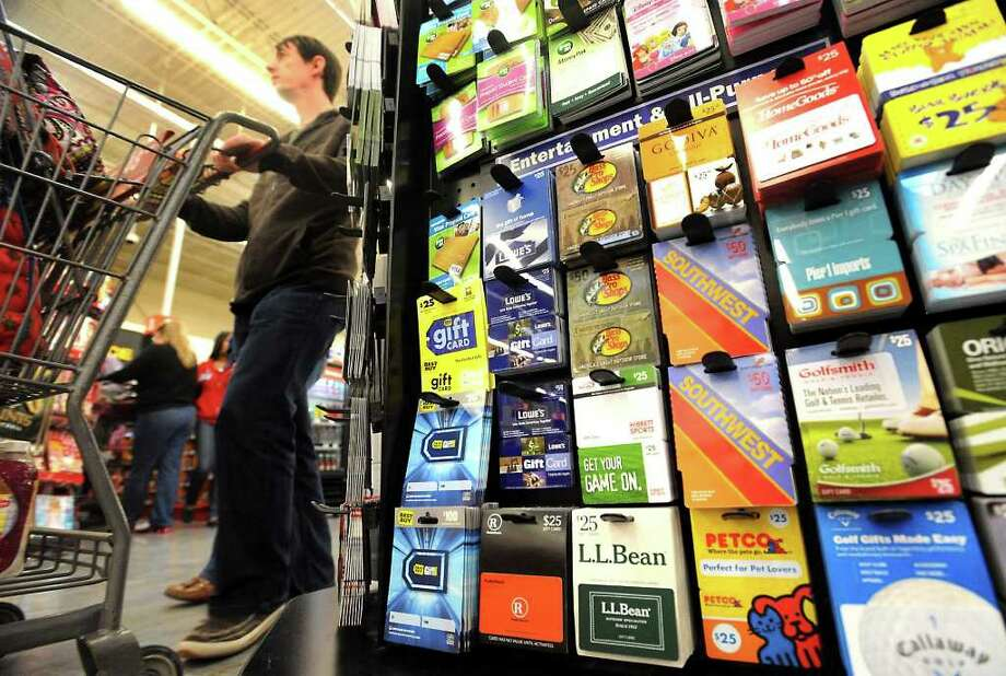 Shoppers walk by the gift card center at H-E-B in Beaumont, Saturday. Tammy McKinley/The Enterprise Photo: TAMMY MCKINLEY / Beaumont