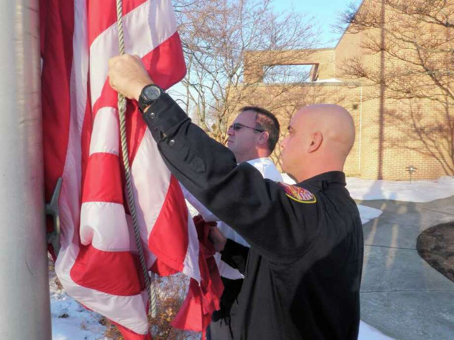 Westport fire Lt. Tom Richmond and Firefighter Nick Marsan lower the service flag that flew on the pole at Fire Department headquarters since they left to serve with the Connecticut National Guard in Afghanistan and Iraq. Photo: Contributed Photo / Westport News contributed