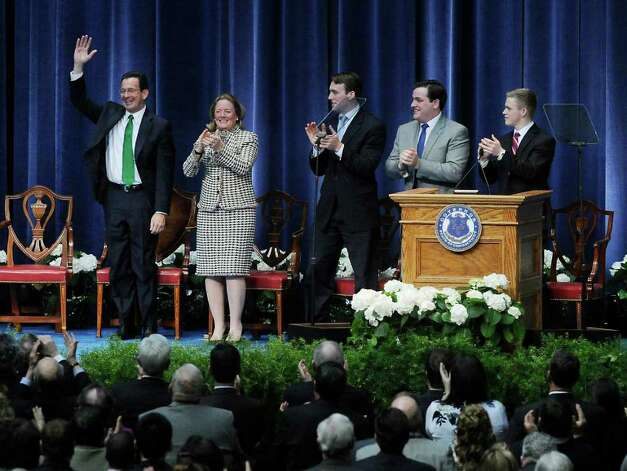 Governor Dan Malloy waves to the crowd after taking the the oath of office as 88th governor of the State of Conn.  He stands with his wife Cathy Malloy and sons Dan, Ben and Sam Malloy at the State Armory in Hartford, Conn. on Wednesday, January 5, 2011. Photo: Kathleen O'Rourke / Stamford Advocate