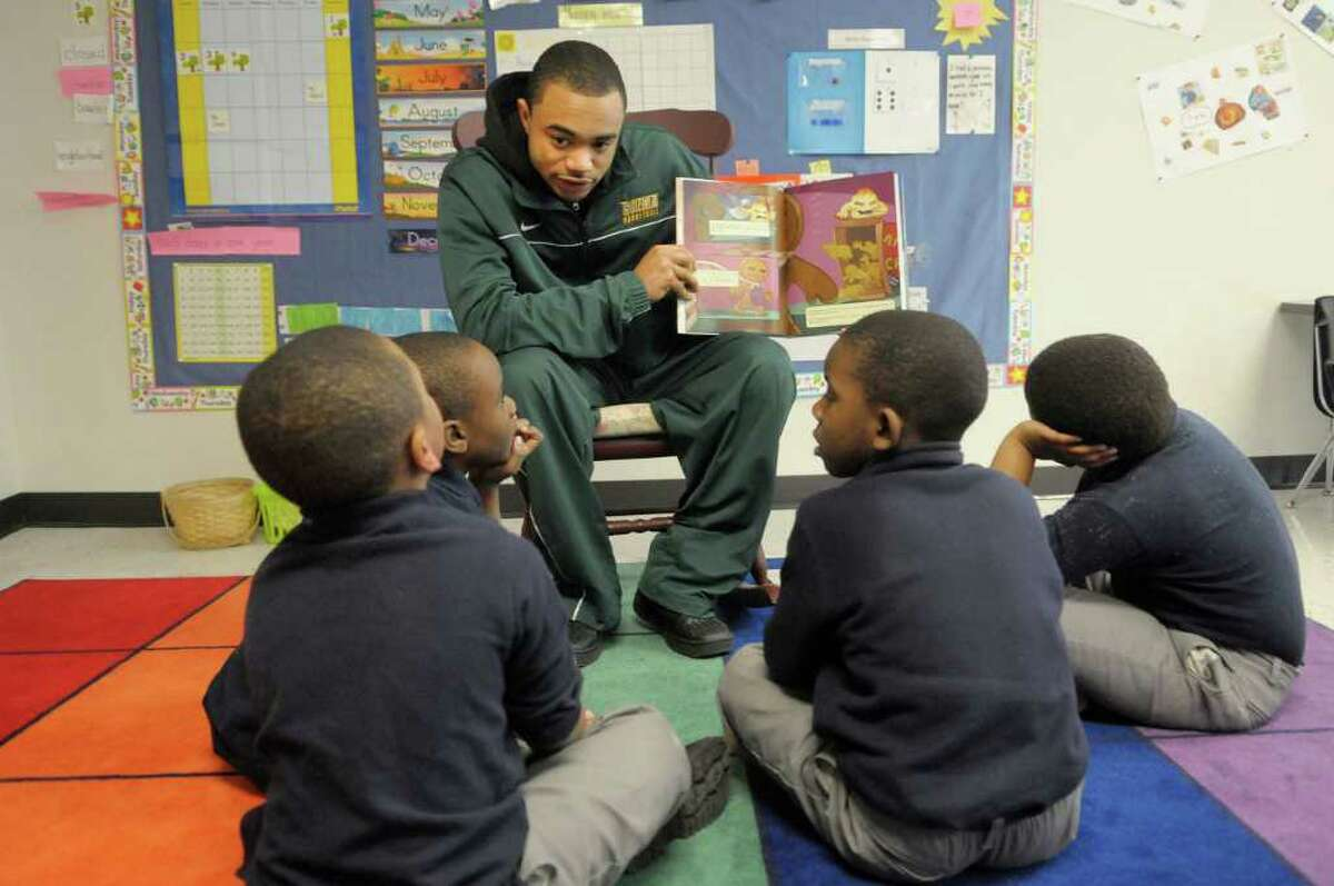 Siena basketball player Rakeem Brookins reads to first graders at Brighter Choice Charter School in Albany.. (Paul Buckowski / Times Union)