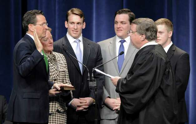 With his wife Cathy and sons at his side, Dan Malloy, left, is sworn in as Connecticut's 88th governor by the Honorable Gerald Fox, right, inside the Hartford State Armory in Hartford Conn., Wednesday, Jan. 5, 2011. (AP Photo/Sean D. Elliot, Pool) Photo: AP