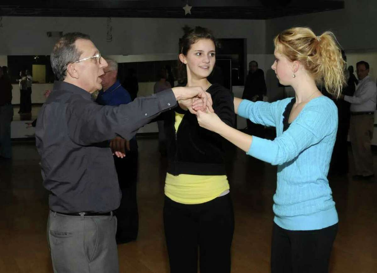 John Vitti, left, owner of Vitti's Dance Studio, in Danbury, coaches sisters, Pearl Scalzo, center, and Chelsea Scalzo, right, both of Brookfield, during an intermediate level dance class, on Tuesday, Jan. 4, 2011.