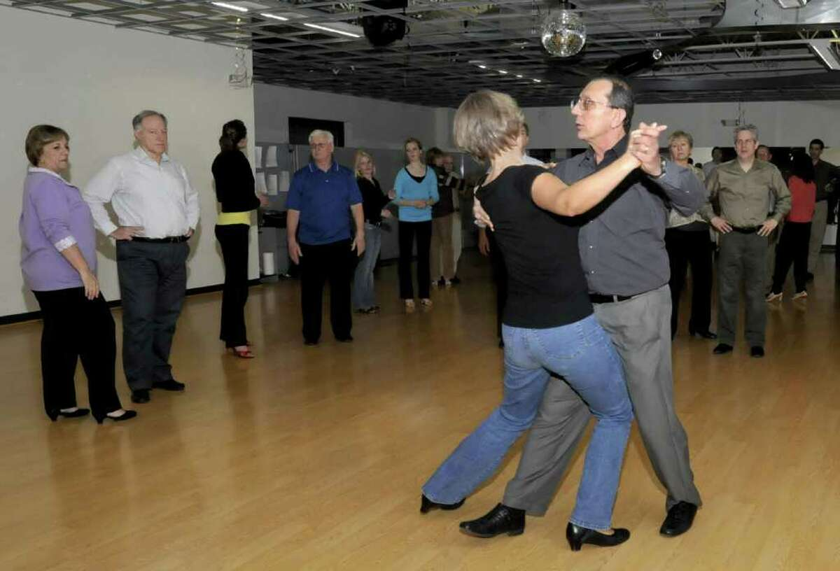 Lorette Pugner, left, of Danbury, and, Charles Rodriguez, 2nd from left, of Bethel, look on as John Vitti, owner of Vitti's Dance Studio, in Danbury, demonstrates a dance move with Ivana Pilepich,of Bethel, during an intermediate level dance class, on Tuesday, Jan. 4, 2011.