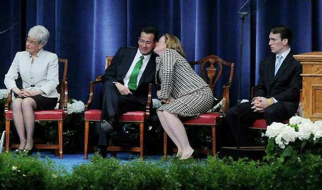 "Cathy Malloy kisses her husband, Gov., Dannel P. Malloy as ""Danny Boy"" is performed by Mary Fox during the Inauguration Ceremony at the State Armory in Hartford Wednesday. Photo: Kathleen O'Rourke, ST / Stamford Advocate"