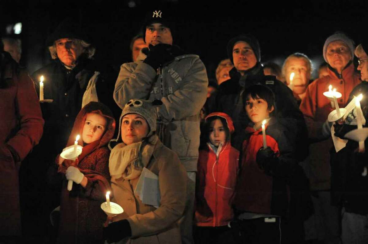 A group of seventh graders from Nicholas Naumkin's school hold a candlelight vigil and sing songs in his memory of him and his grandfather Oleg Moston in Congress Park in Saratoga Spings on Wednesday. (Lori Van Buren / Times Union)