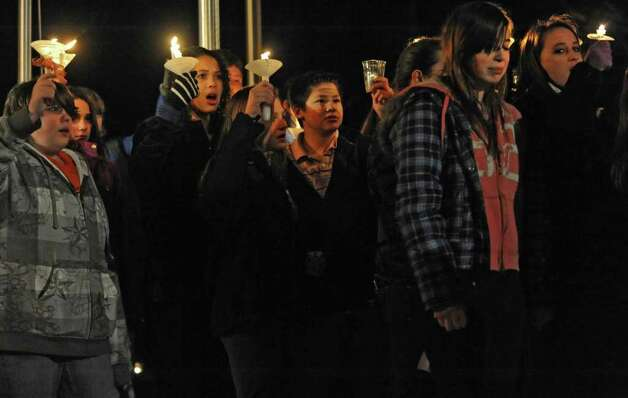Seventh-graders from Nicholas Naumkin's school hold a candlelight vigil and sing songs in his memory of him and his grandfather Oleg Moston in Congress Park in Saratoga Spings.  (Lori Van Buren / Times Union) Photo: Lori Van Buren