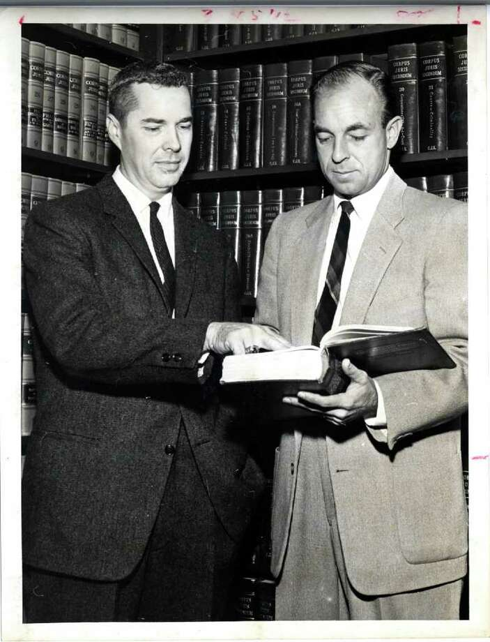 "Frank Briscoe, left, and Wallace C. ""Pete"" Moore look at law book in 1960. Houston Chronicle file photo / Houston Chronicle"
