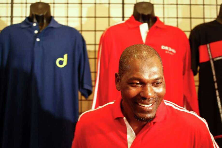 Former NBA star and Rockets player Hakeem Olajuwon shows his new line of clothing DR34M before the Rockets game against Toronto on Dec. 31 in Houston. Michael Paulsen/Houston Chronicle / Houston Chronicle