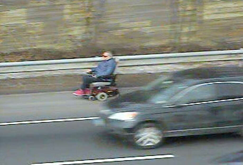 A man rides an electric wheelchair in the shoulder of I-95 in Fairfield on Thursday afternoon. Photo: Contributed Photo / Connecticut Post Contributed