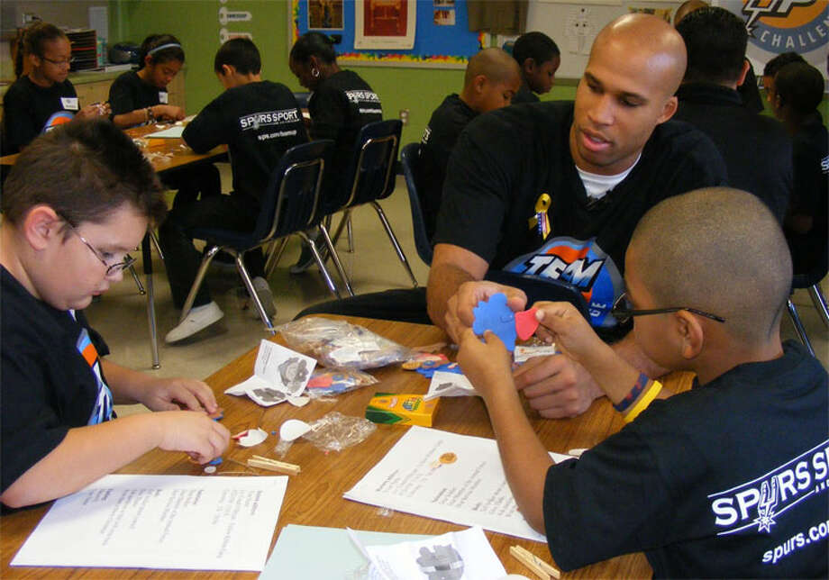 San Antonio Spur Richard Jefferson helps two Converse Elementary School students with pre-Christmas crafts event. Jefferson and fellow Spur Gary Neal visited the school as part of the Team Up Challenge.Photo by Jeff B. Flinn