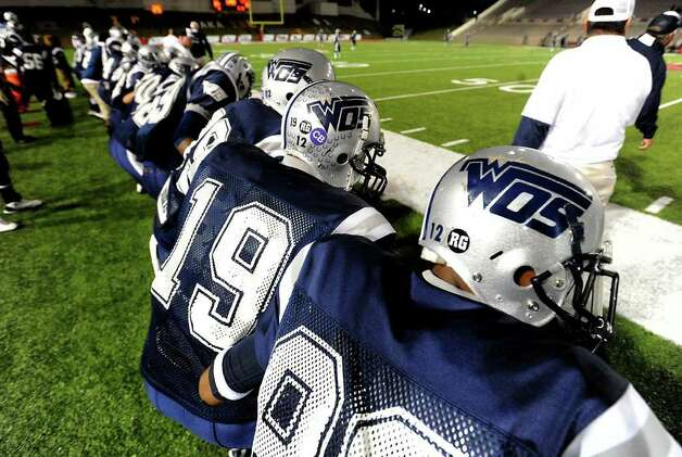 The WOS Mustangs wear the number of fallen quarterback, Reggie Garrett on thier helmuts during the play off game against Liberty at Provost  Umphrey Stadium at Lamar, Friday. Tammy McKinley/The Enterprise Photo: TAMMY MCKINLEY / Beaumont