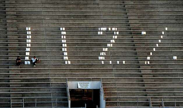 Luminaries spell out 112% in the visitors stands during the Reggie Garrett memorial service at West Orange-Stark High School in West Orange, Friday. Tammy McKinley/The Enterprise Photo: TAMMY MCKINLEY / Beaumont