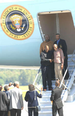 "Members of the Dickson family pose for pictures with father, Joe Dickson, at left bottom, and son Staff Sgt. Reggie Dickson, left top, a steward on the steps of Air Force One at the Albany International Airport on Monday, Sept 21, 2009.  The family of the steward, who lives in Albany, was granted a tour of the ""First Plane"" while President Obama  was on his tour and speech at Hudson Valley Community College.  (Luanne M. Ferris / Times Union)"