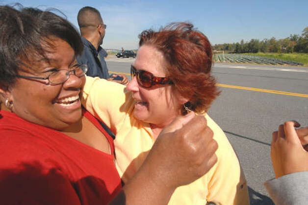 Jen Biaz, of Saratoga Springs, left, and Christine Van Ullen of Cohoes, right, were overcome with emotion after seeing President Barack Obama wave to them on Albany Shaker Rd. Monday morning. Hundreds lined the road outside Albany International Airport hoping to catch a glimpse of the President who spoke at Hudson Valley Community College. (Will Waldron / Times Union)