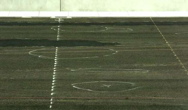 "White and blue circles can be seen on the rubber surface currently covering the playing field at the new Dr.Carrol A. ""Butch"" Thomas Educational Support Center football stadium.  Possible problems have developed with a least a dozen spots below ground rising up several inches and causing an un-level playing surface.  Soil tests are being done with results expected back soon.     Dave Ryan/The Enterprise Photo: Dave Ryan / Beaumont"